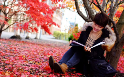 woman reading a book under a tree surrounded by fallen red coloured leaves