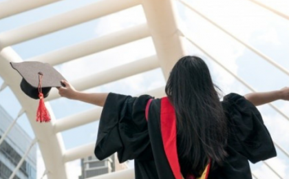 woman in graduation gown and cap holding her diploma