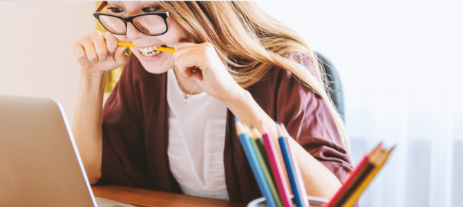 Woman staring at a computer looking angry while she chews on a yellow pencil